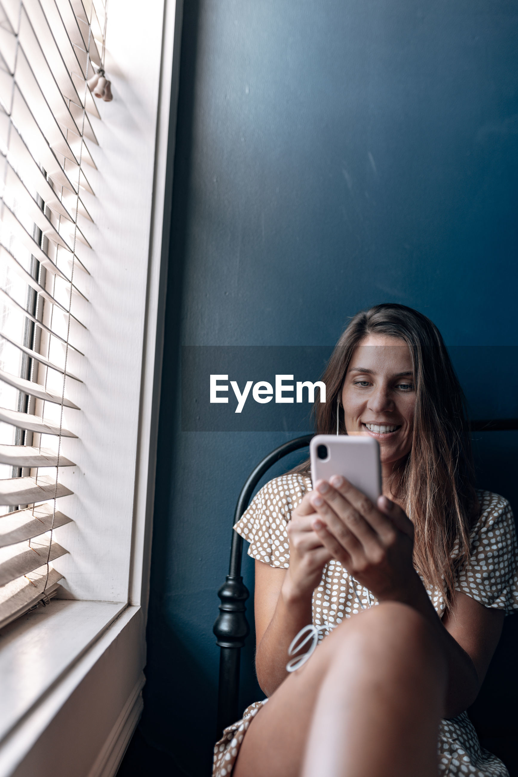 Woman on video call while sitting by window