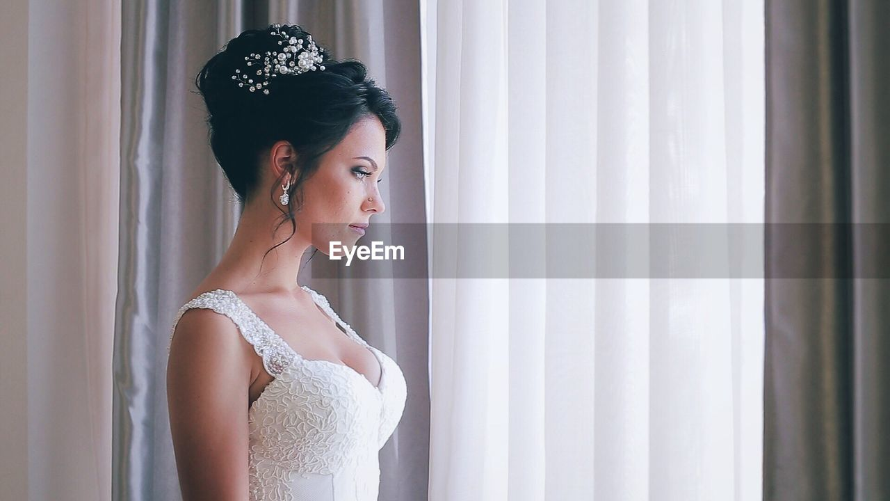 Thoughtful Bride Standing By Curtain At Home