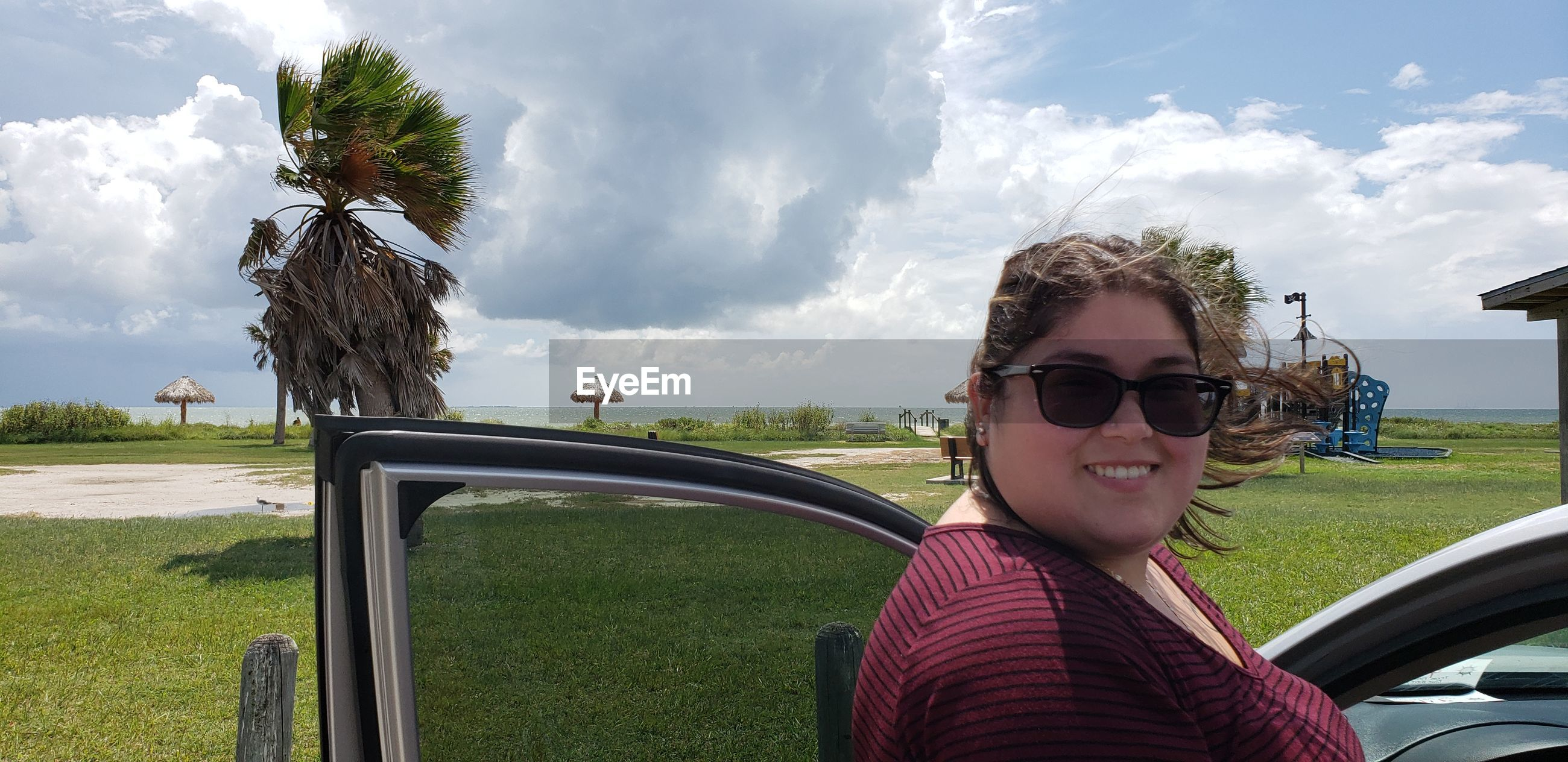 Portrait of smiling woman wearing sunglasses standing by car