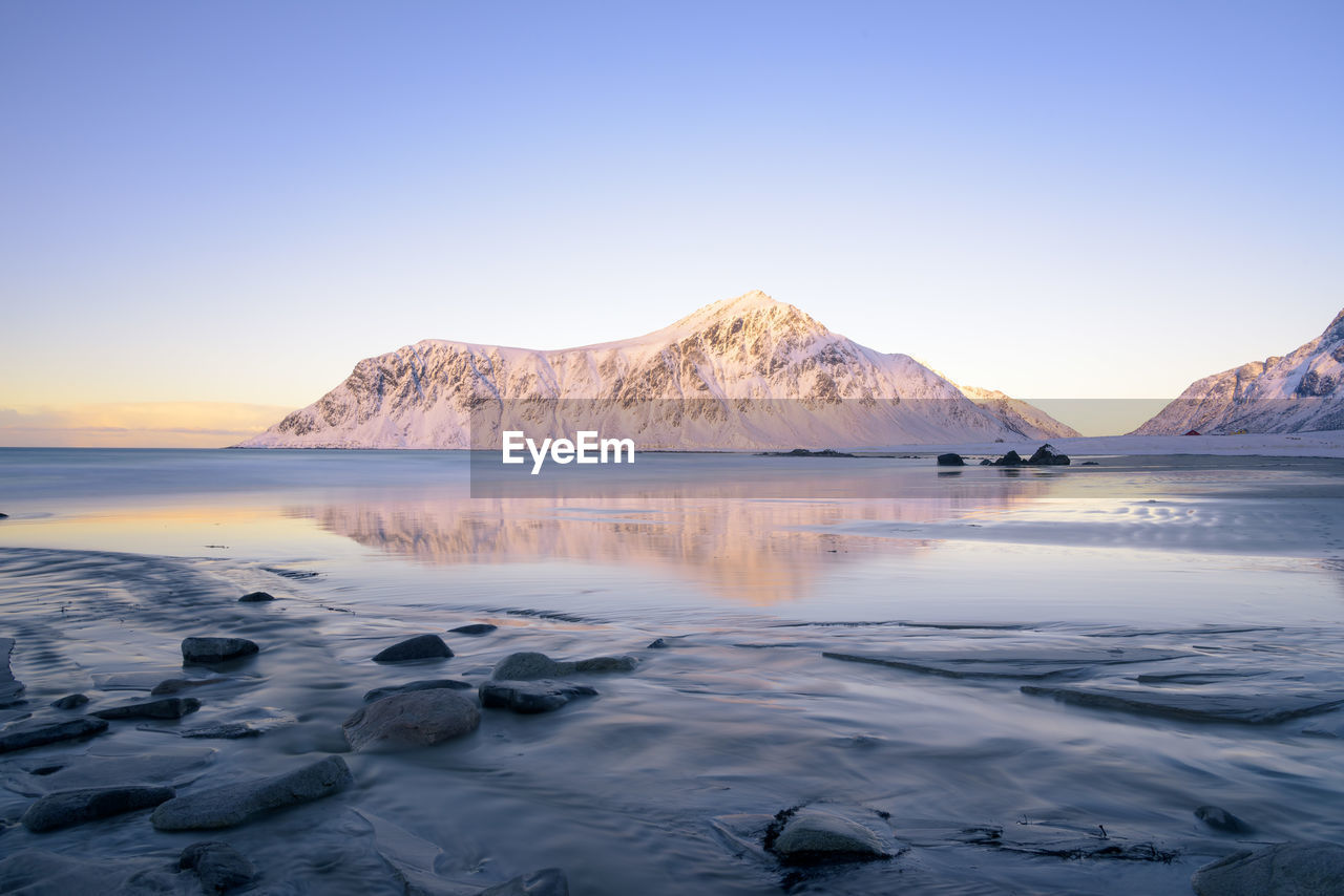 Scenic View Of Sea And Snowcapped Mountains Against Clear Sky During Sunset