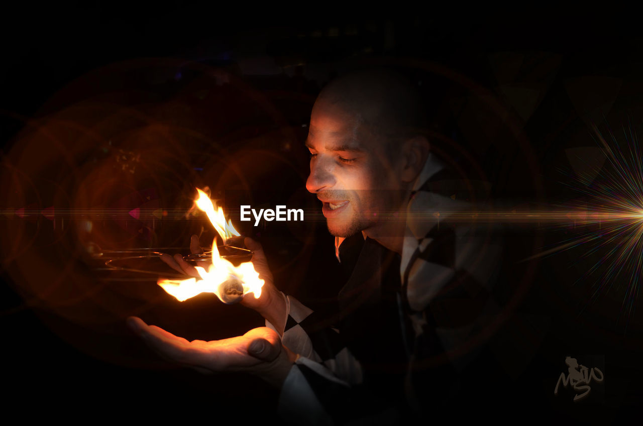 DIGITAL COMPOSITE IMAGE OF YOUNG MAN WITH FIRE IN THE DARK