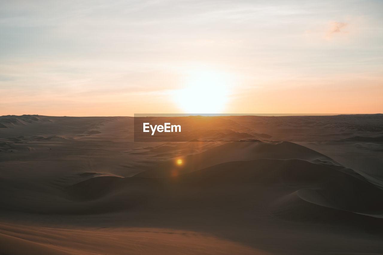 sky, sunset, beauty in nature, scenics - nature, tranquility, tranquil scene, sun, cloud - sky, non-urban scene, land, nature, sunlight, idyllic, sand, landscape, no people, sunbeam, lens flare, sand dune, desert, arid climate, outdoors, climate, bright