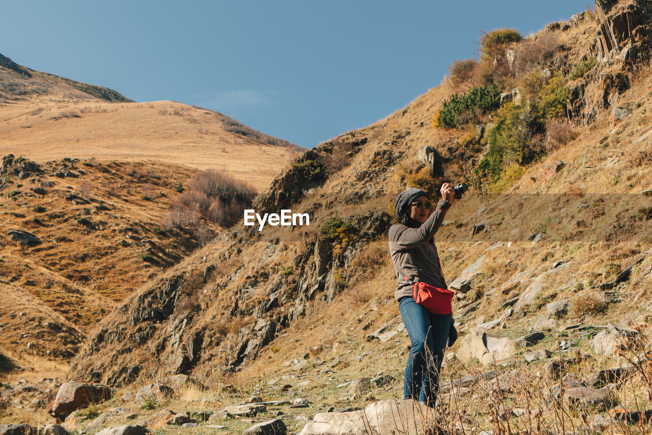Rear view of man photographing on mountain against sky