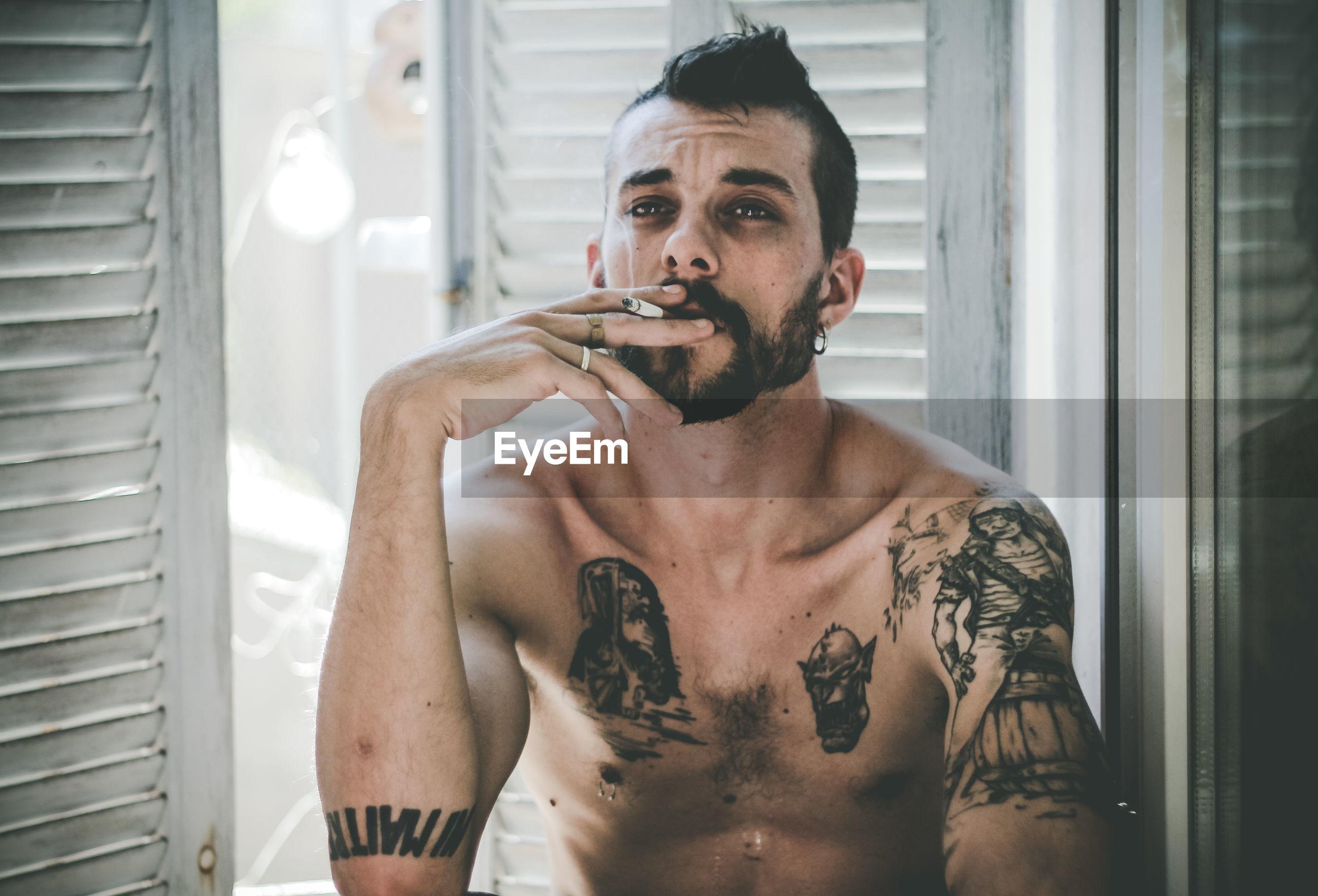 Close-up of shirtless man smoking cigarette at home