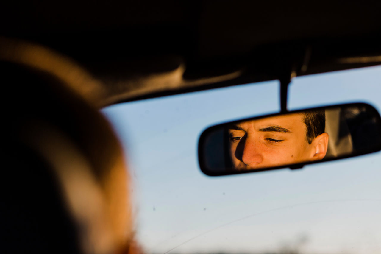 Reflection Of Man On Rear-View Mirror In Car