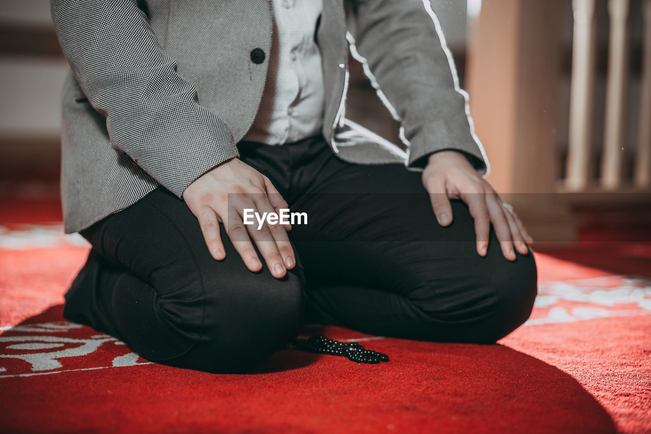 MIDSECTION OF COUPLE SITTING IN HANDS