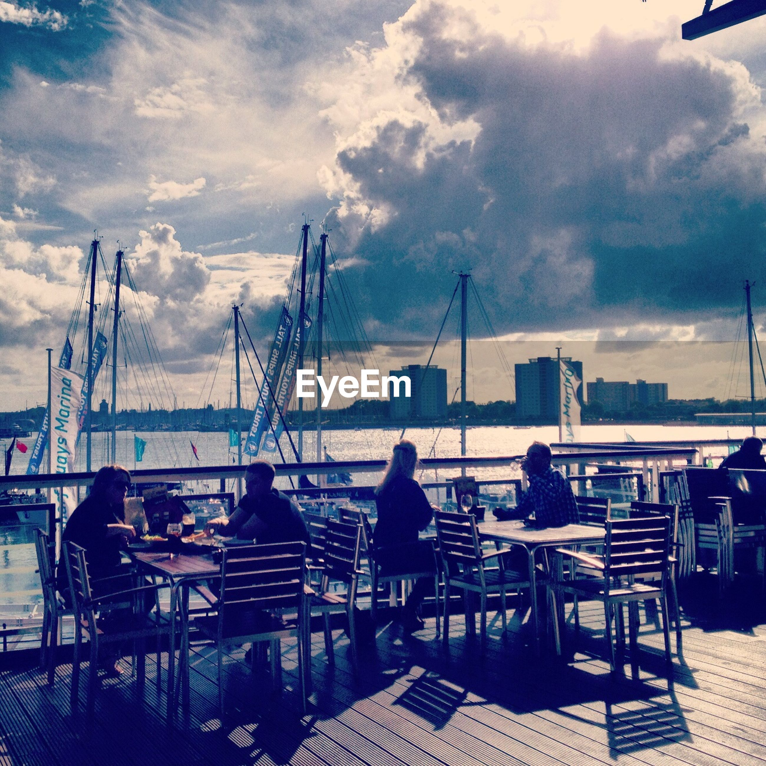 sky, nautical vessel, cloud - sky, water, chair, moored, sea, transportation, harbor, mode of transport, cloud, cloudy, boat, sitting, restaurant, table, men, building exterior, city