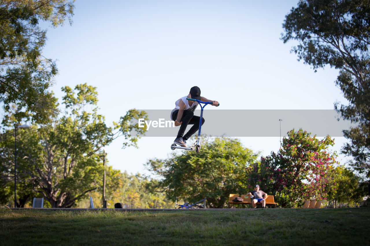 tree, full length, mid-air, jumping, men, day, leisure activity, real people, casual clothing, clear sky, lifestyles, motion, outdoors, nature, sport, sky, one person, grass, energetic, adult, people