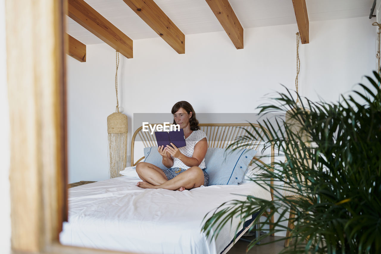 WOMAN SITTING ON BED WITH MAN USING PHONE