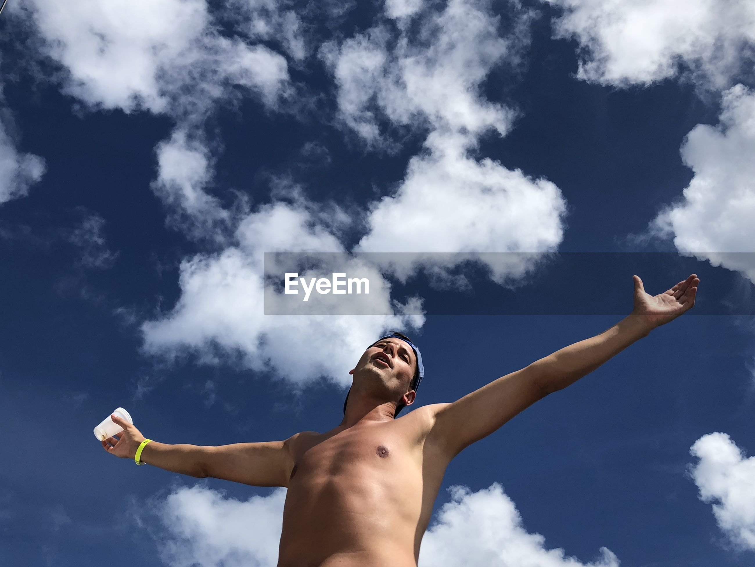Low angle view of shirtless man with arms outstretched against sky