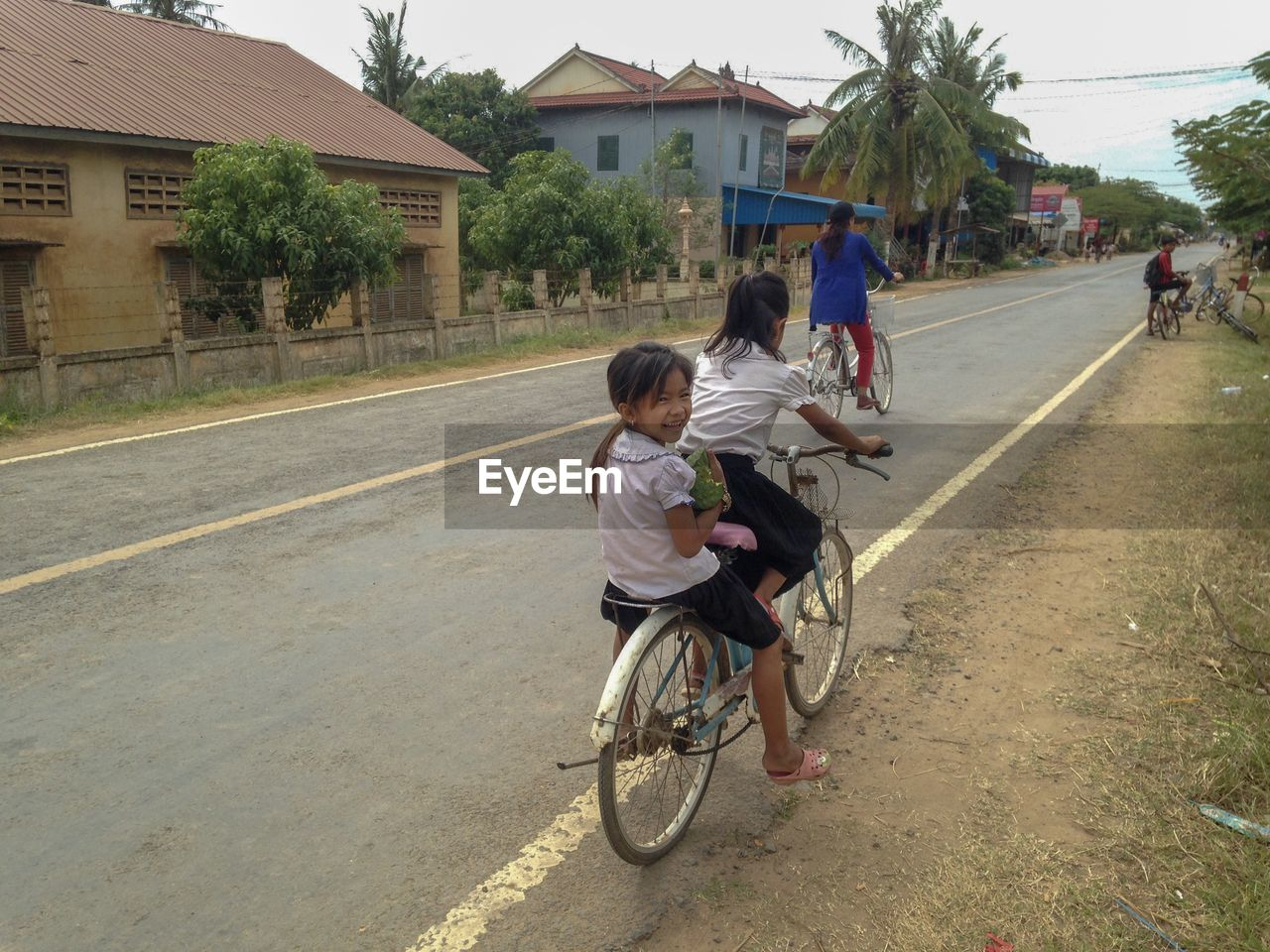 transportation, real people, child, men, childhood, bicycle, road, lifestyles, full length, group of people, males, boys, women, building exterior, people, land vehicle, females, riding, casual clothing, outdoors