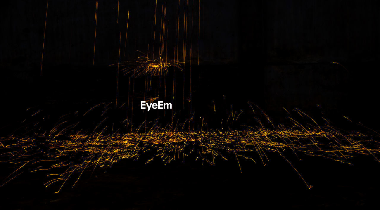 night, illuminated, motion, long exposure, glowing, nature, blurred motion, celebration, no people, firework, dark, light trail, sparks, light, light - natural phenomenon, event, arts culture and entertainment, outdoors, burning, orange color, firework - man made object, firework display, wire wool