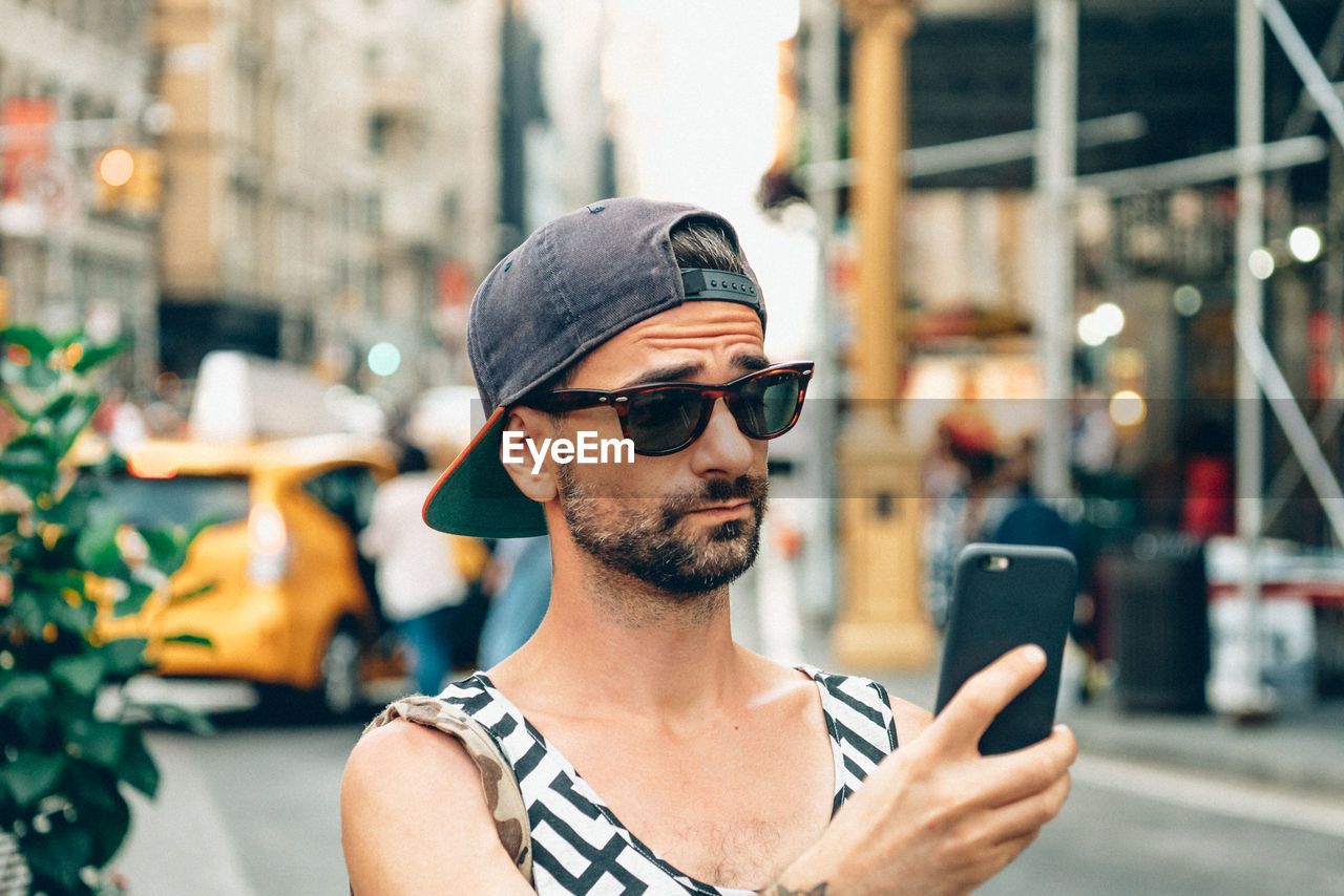 Man taking selfie through smart phone in city