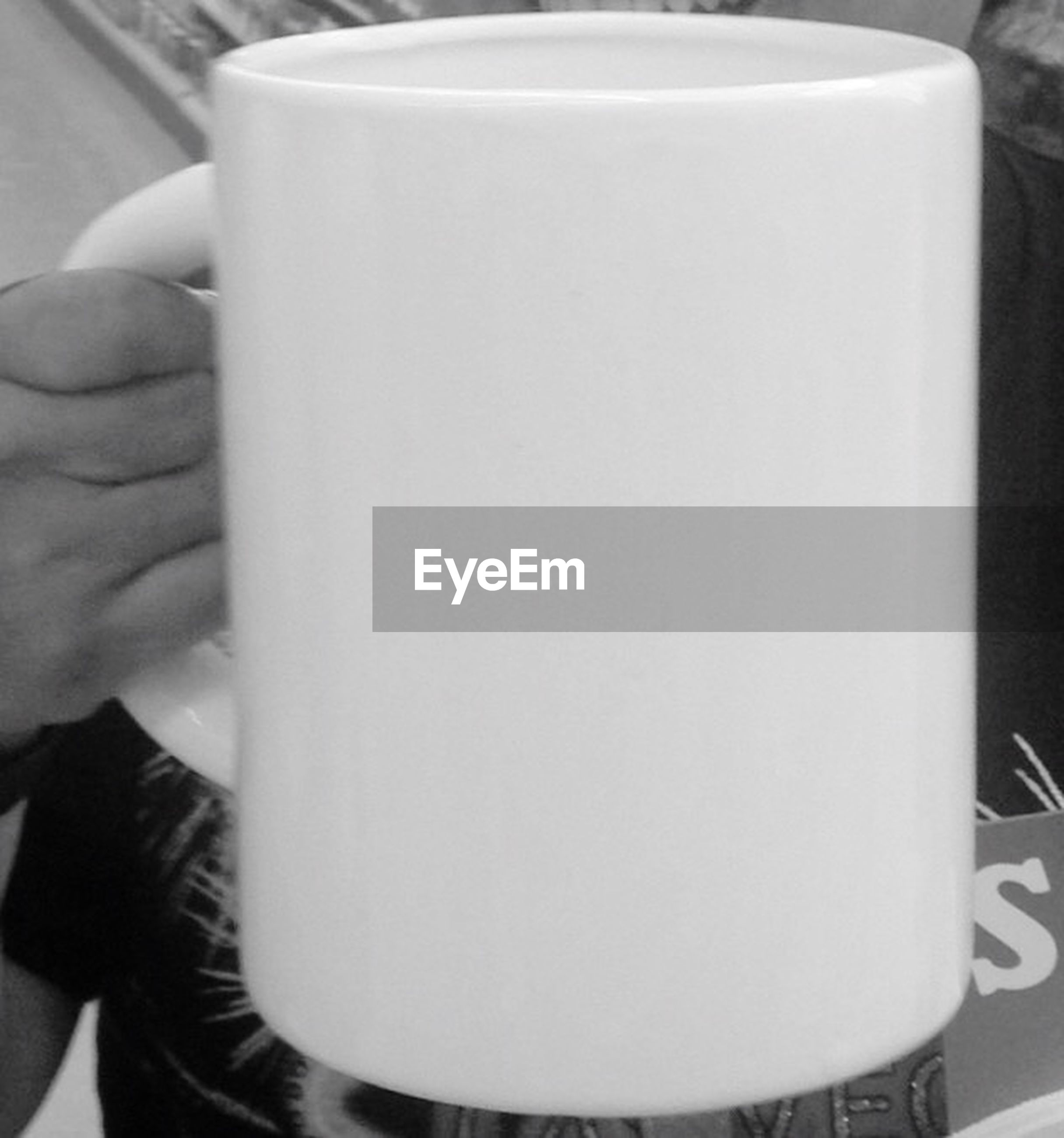 indoors, person, food and drink, drink, holding, coffee cup, cropped, refreshment, part of, close-up, lifestyles, table, unrecognizable person, cup, coffee - drink, focus on foreground