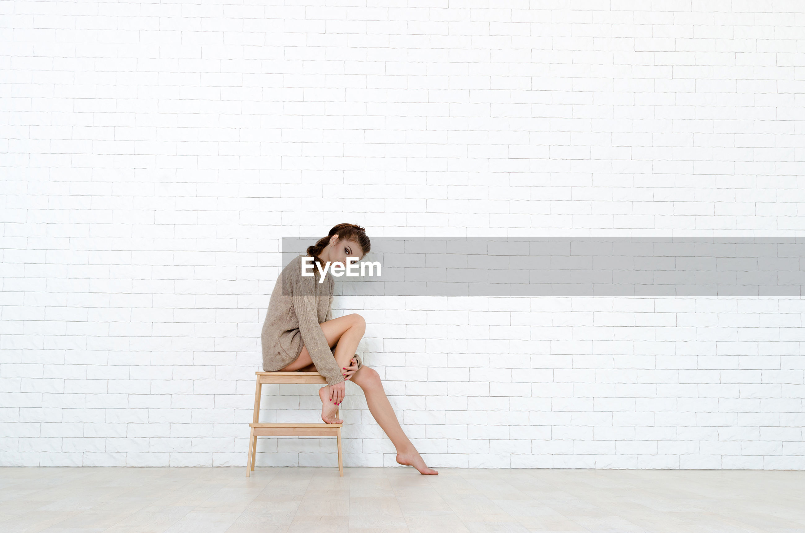 Full length portrait of woman sitting on stool against brick wall