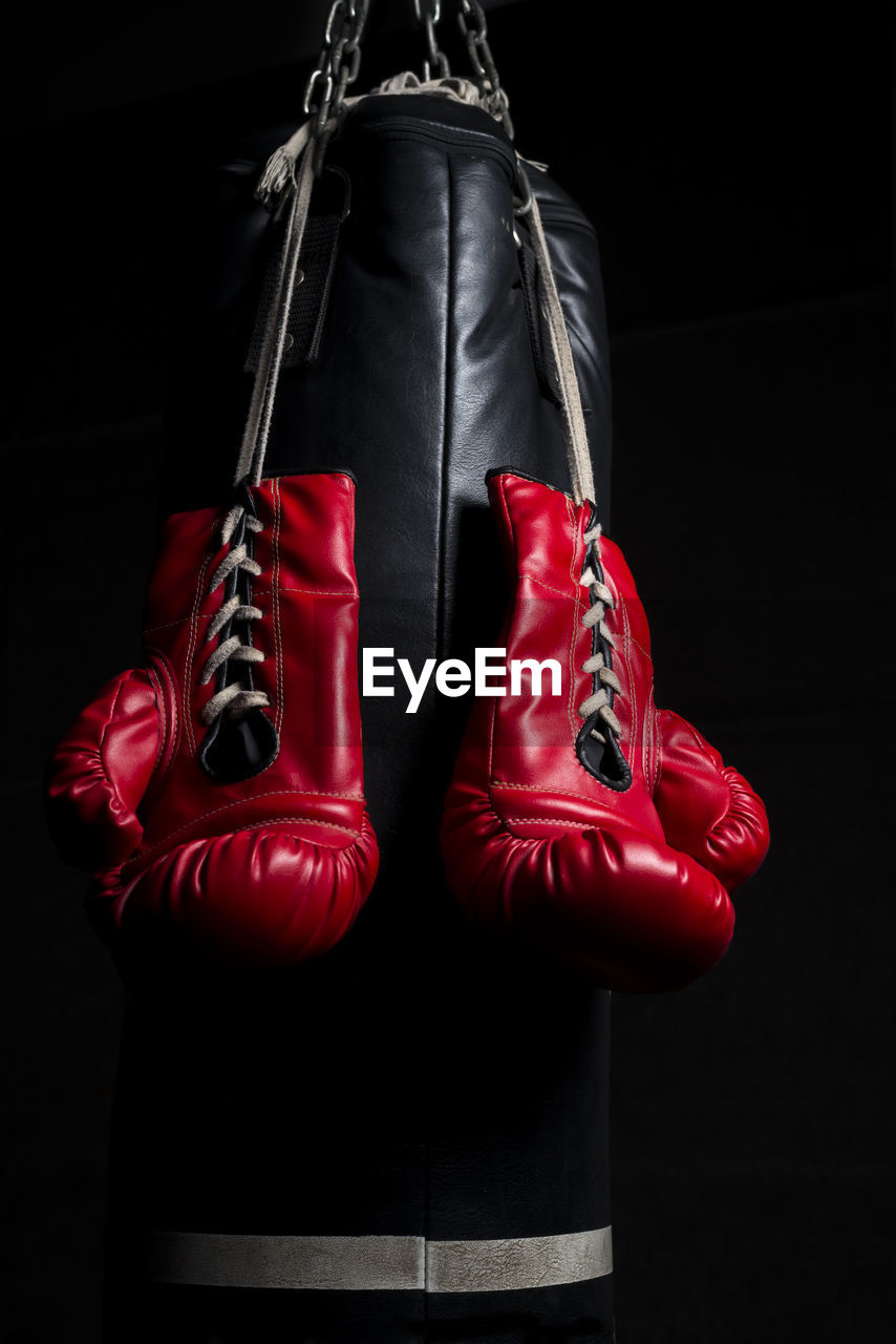 Close-up of boxing gloves hanging against black background