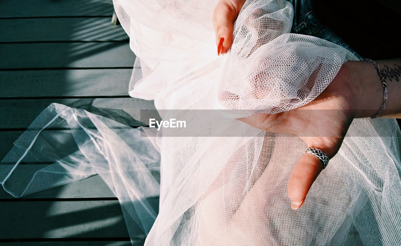 Cropped Hands Of Bride Holding White Veil