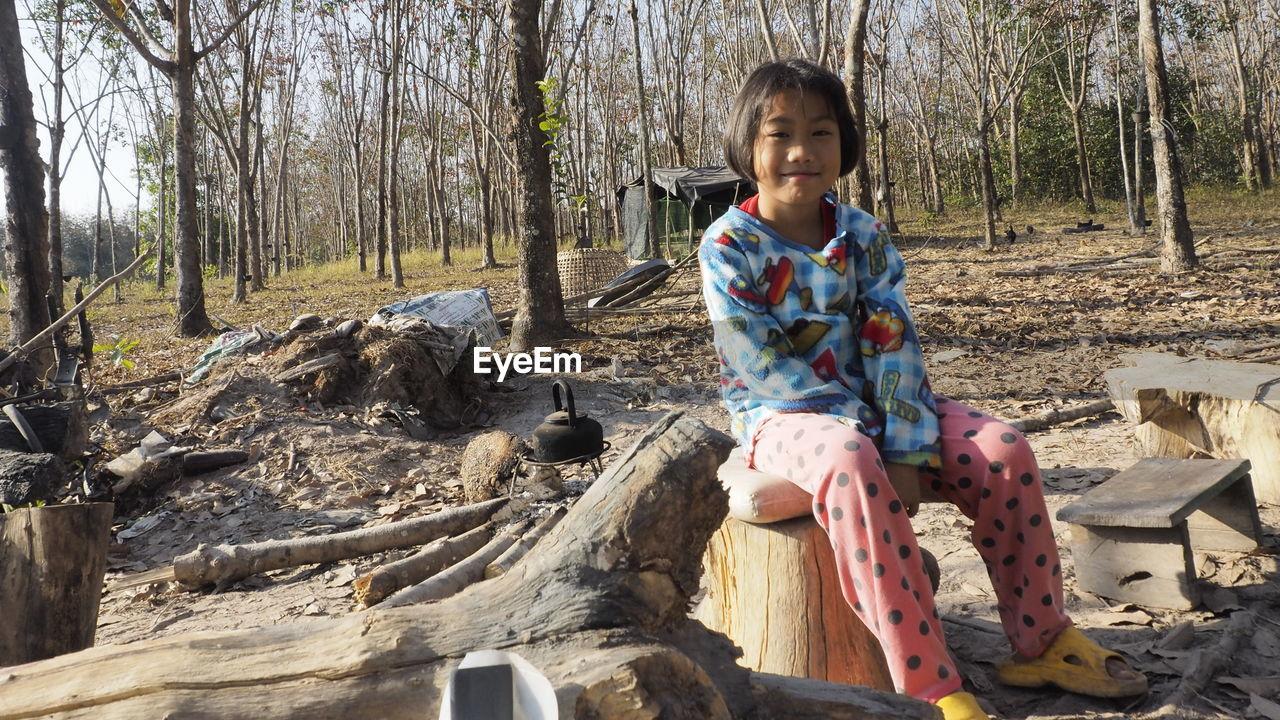 FULL LENGTH PORTRAIT OF GIRL SITTING ON LAND