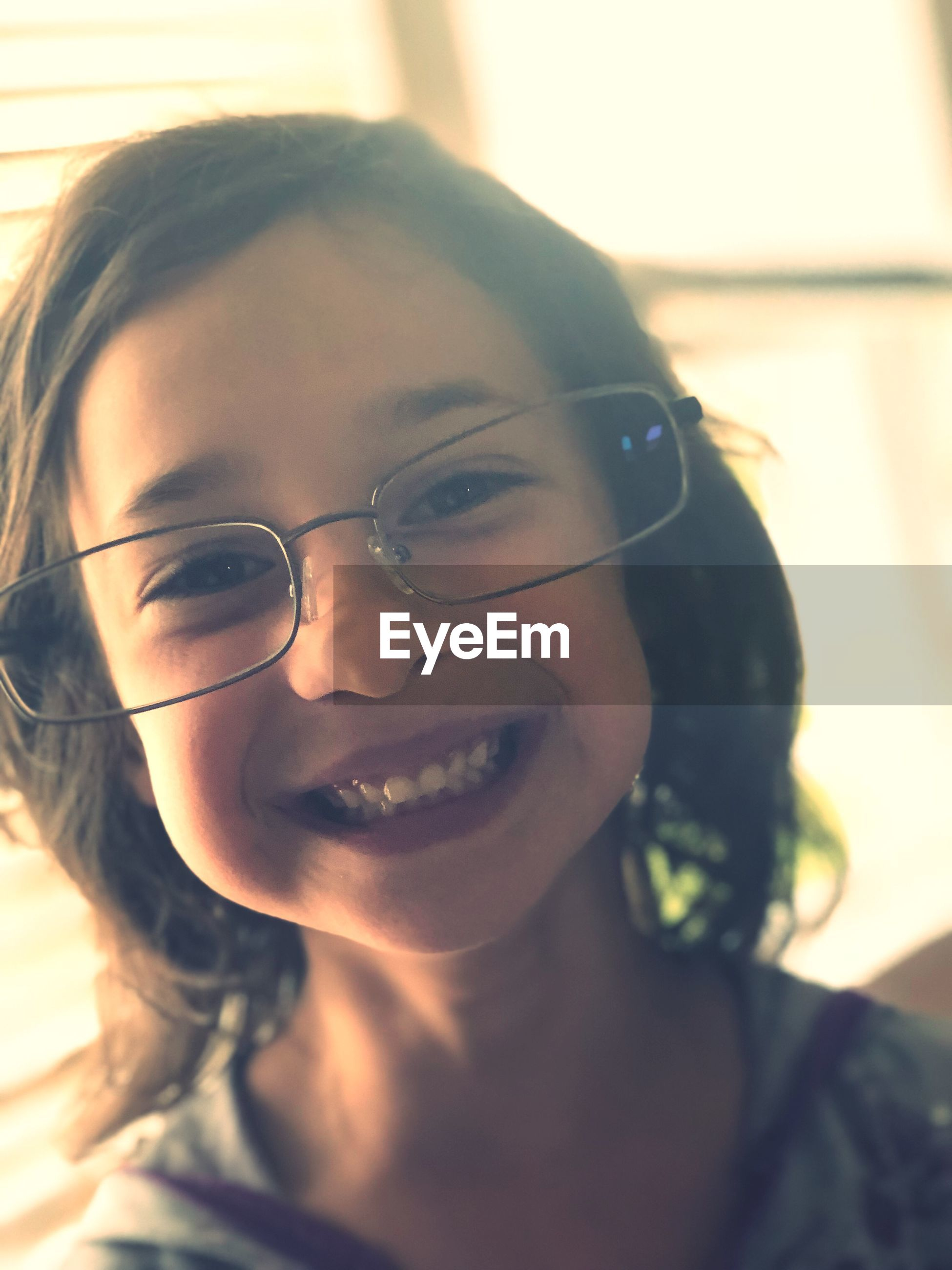 Close-up portrait of smiling girl wearing eyeglasses