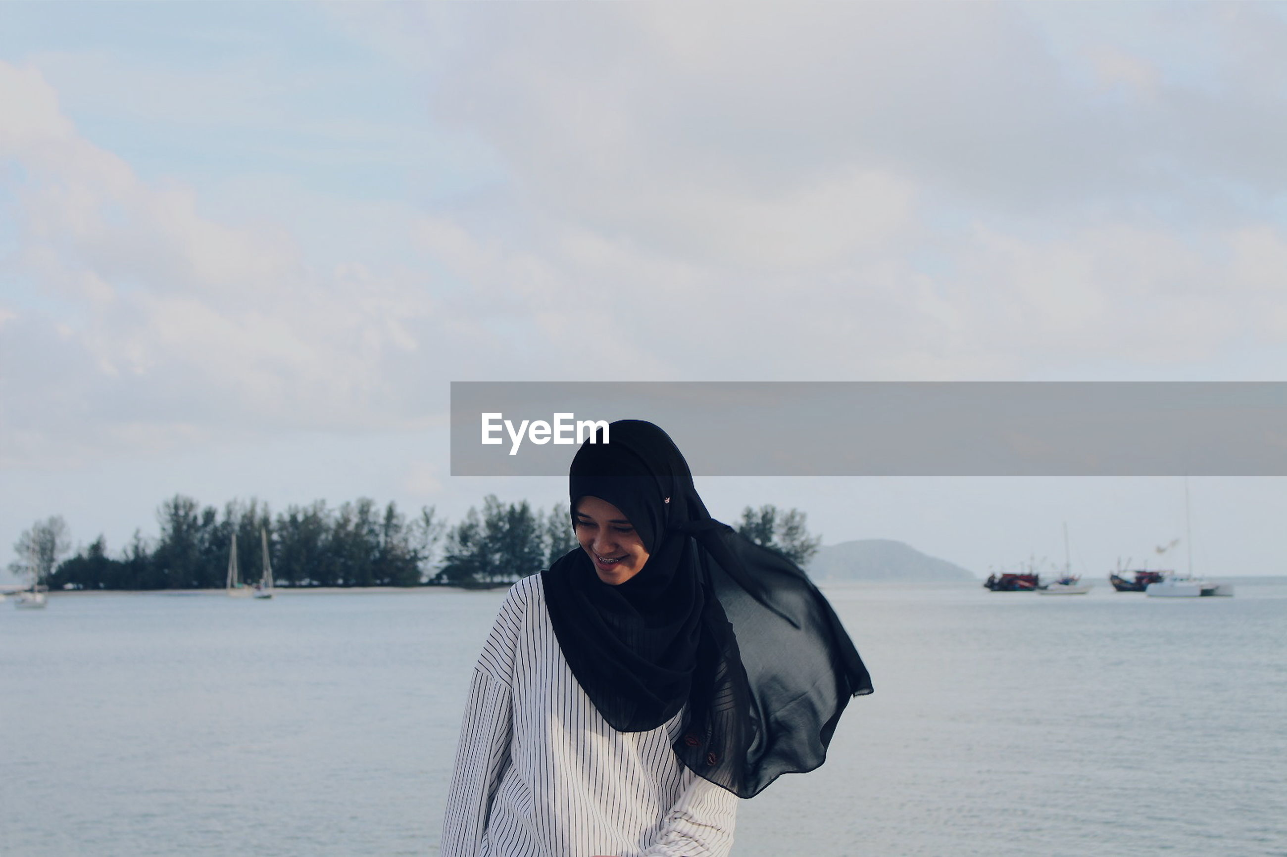 Young woman in hijab standing at beach against cloudy sky
