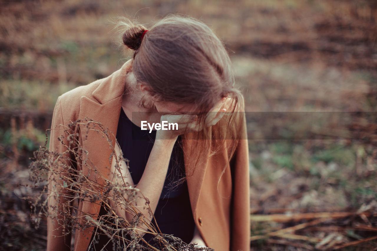 Depressed woman standing on farm