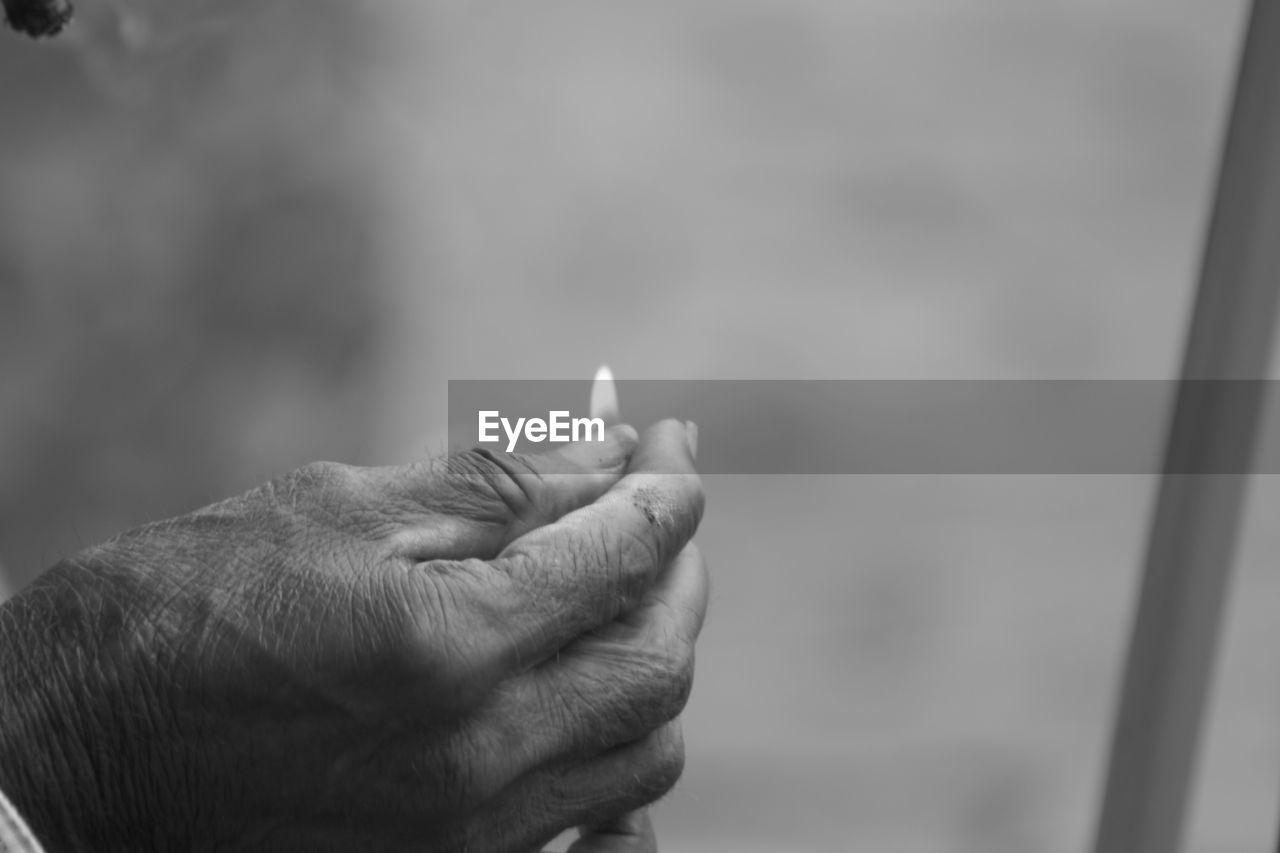 Close-Up Of Hand Holding Lit Match Stick