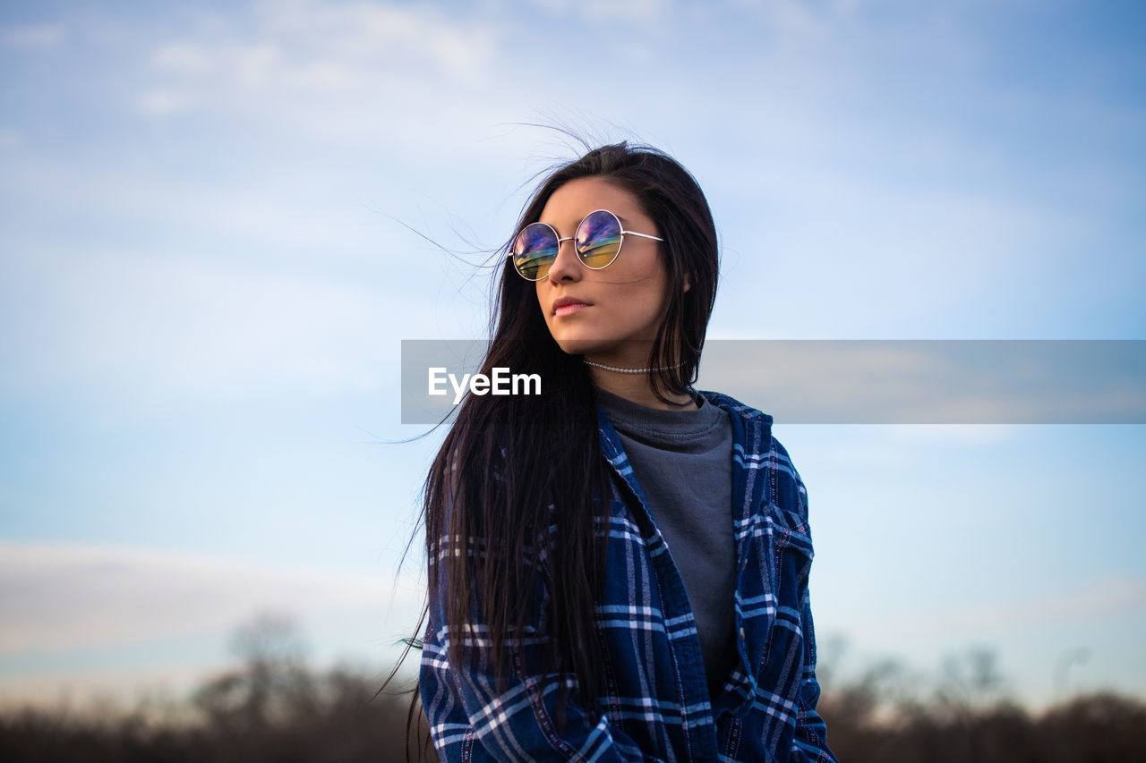 sky, one person, leisure activity, lifestyles, real people, hair, glasses, young adult, nature, hairstyle, long hair, young women, standing, front view, sunglasses, focus on foreground, portrait, cloud - sky, fashion, casual clothing, outdoors, teenager, beautiful woman, wind