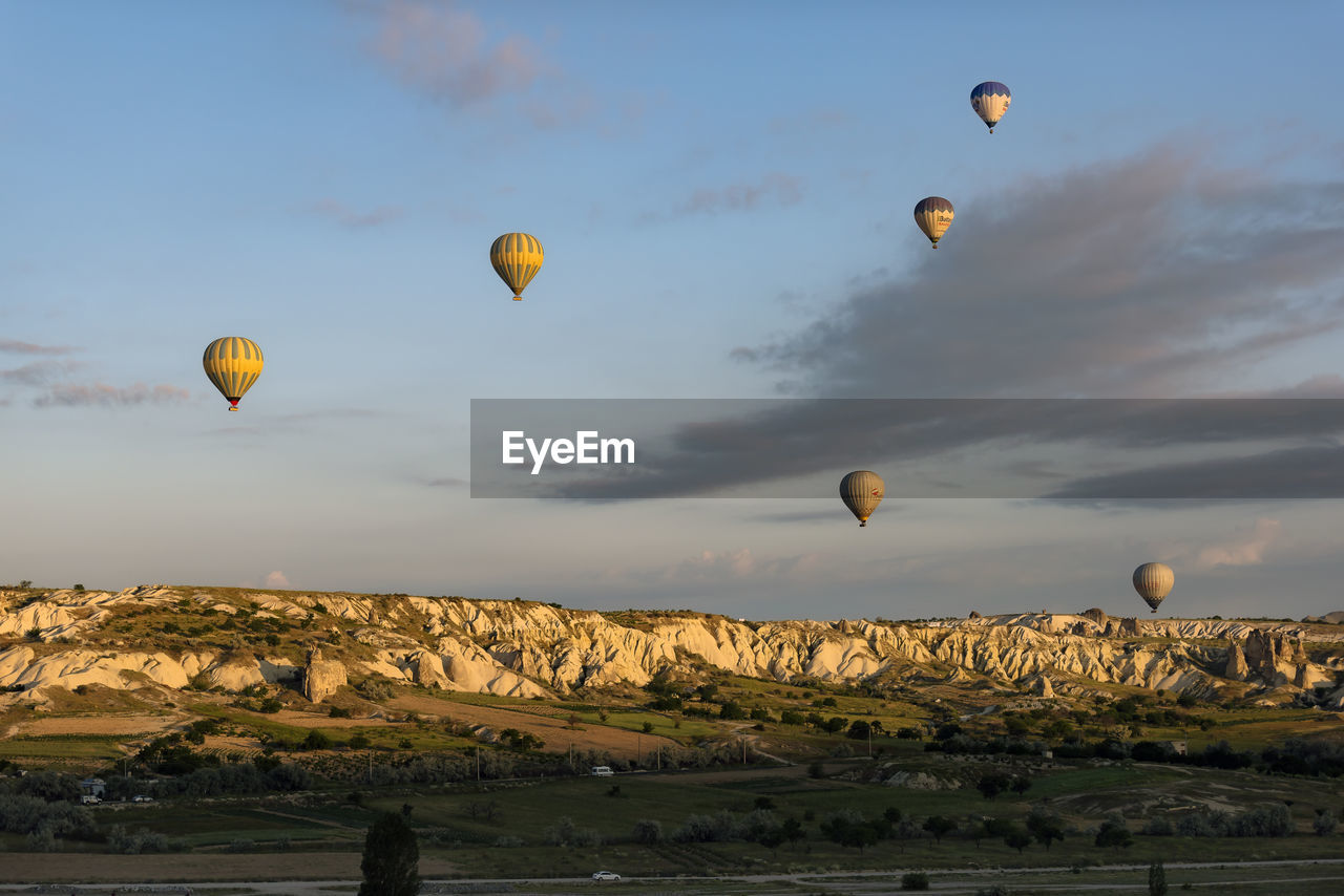 hot air balloon, mid-air, flying, ballooning festival, adventure, transportation, sky, outdoors, landscape, rock - object, air vehicle, nature, sunset, multi colored, rock hoodoo, scenics, balloon, no people, extreme sports, day, beauty in nature, parachute