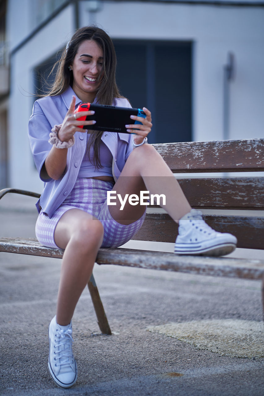 Smiling young woman using mobile phone while sitting on bench outdoors