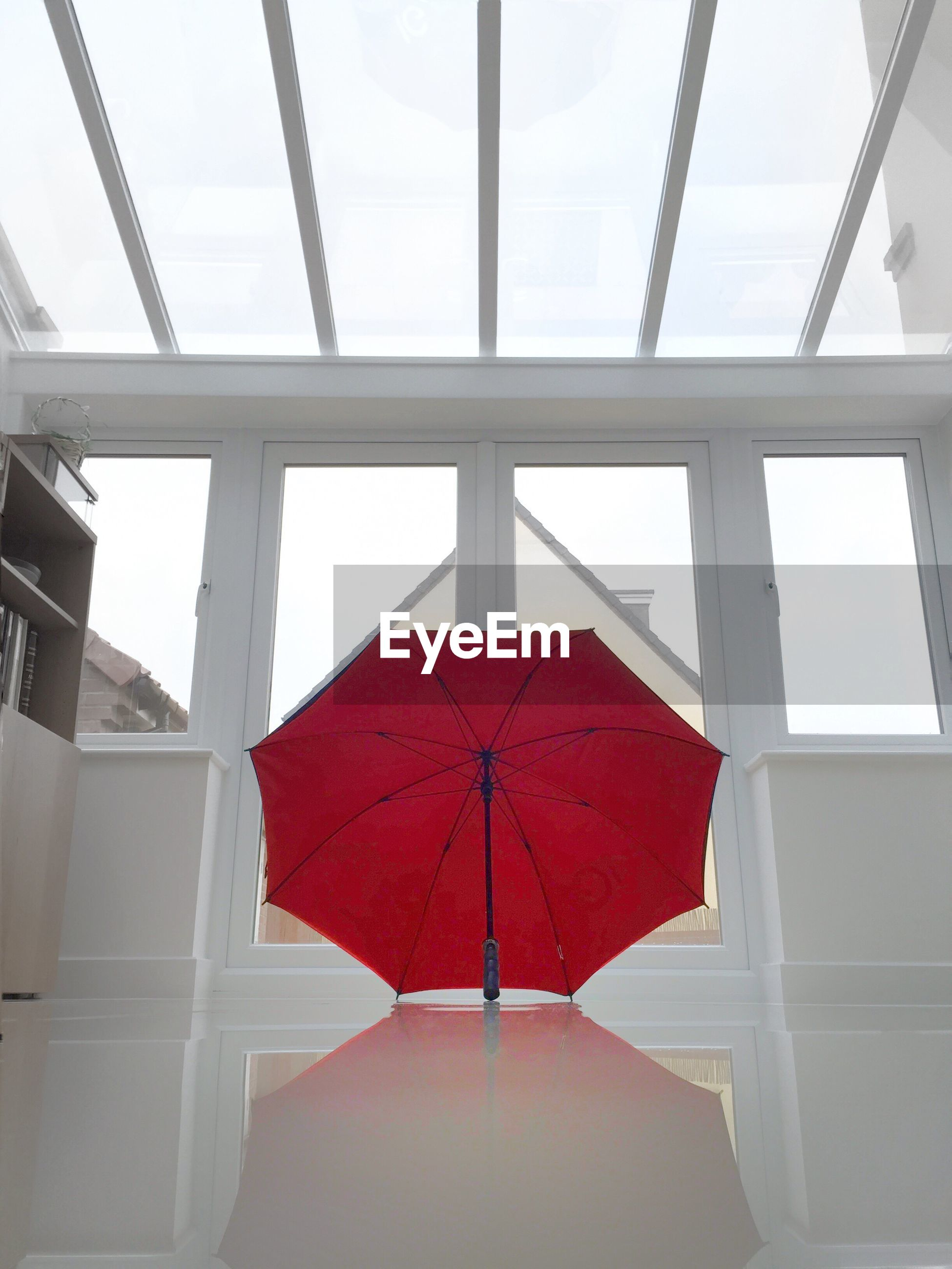 View of a red umbrella on white surface