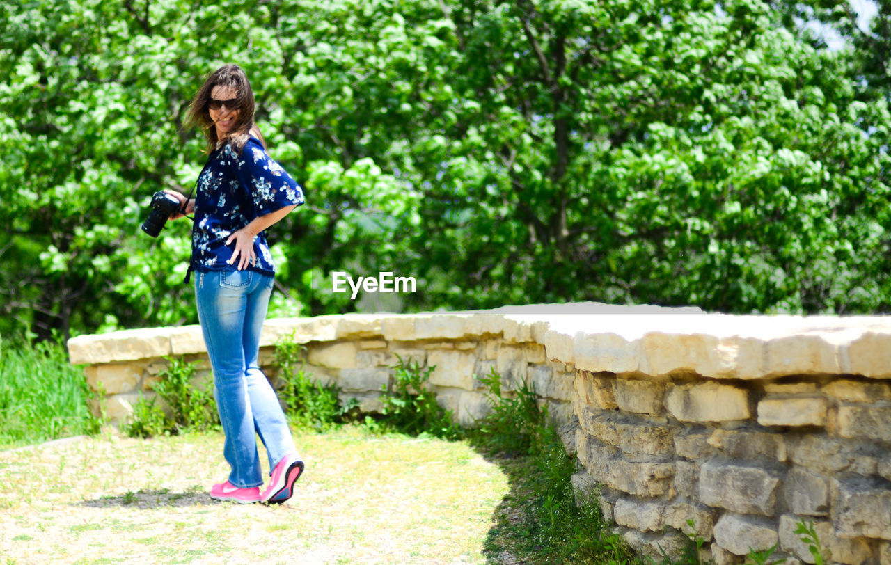 one person, full length, casual clothing, day, nature, plant, standing, women, lifestyles, wall, adult, tree, leisure activity, young adult, outdoors, real people, front view, sunlight, jeans, hairstyle, stone wall