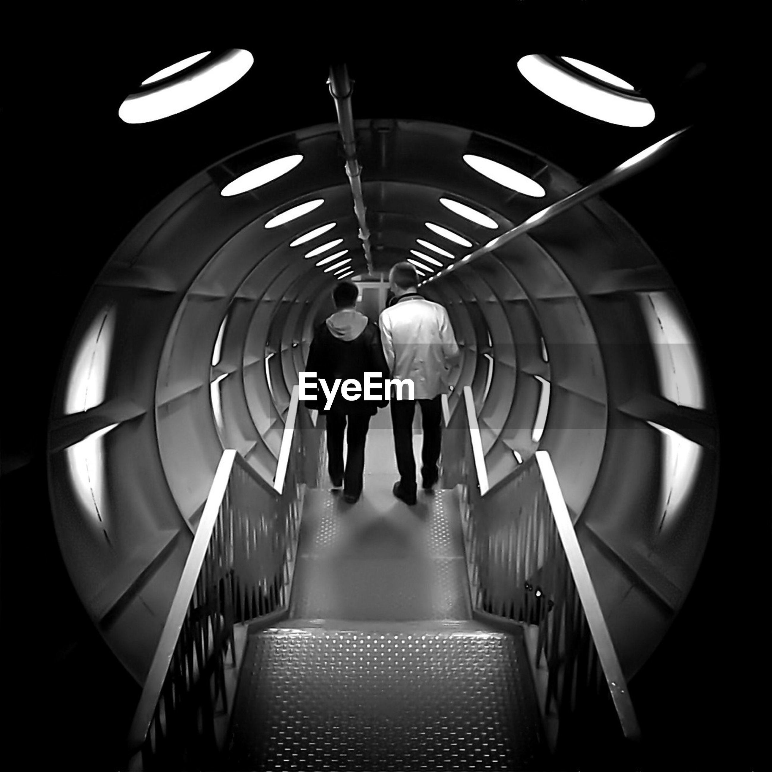 Rear view of men walking inside atomium