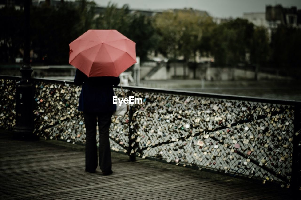 Rear view of woman carrying umbrella standing by padlock covered railing