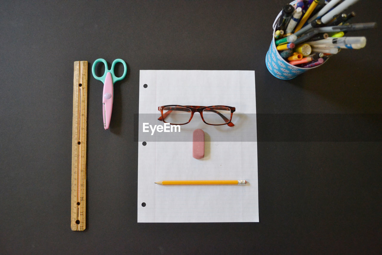 Directly above shot of anthropomorphic face made with stationary on table