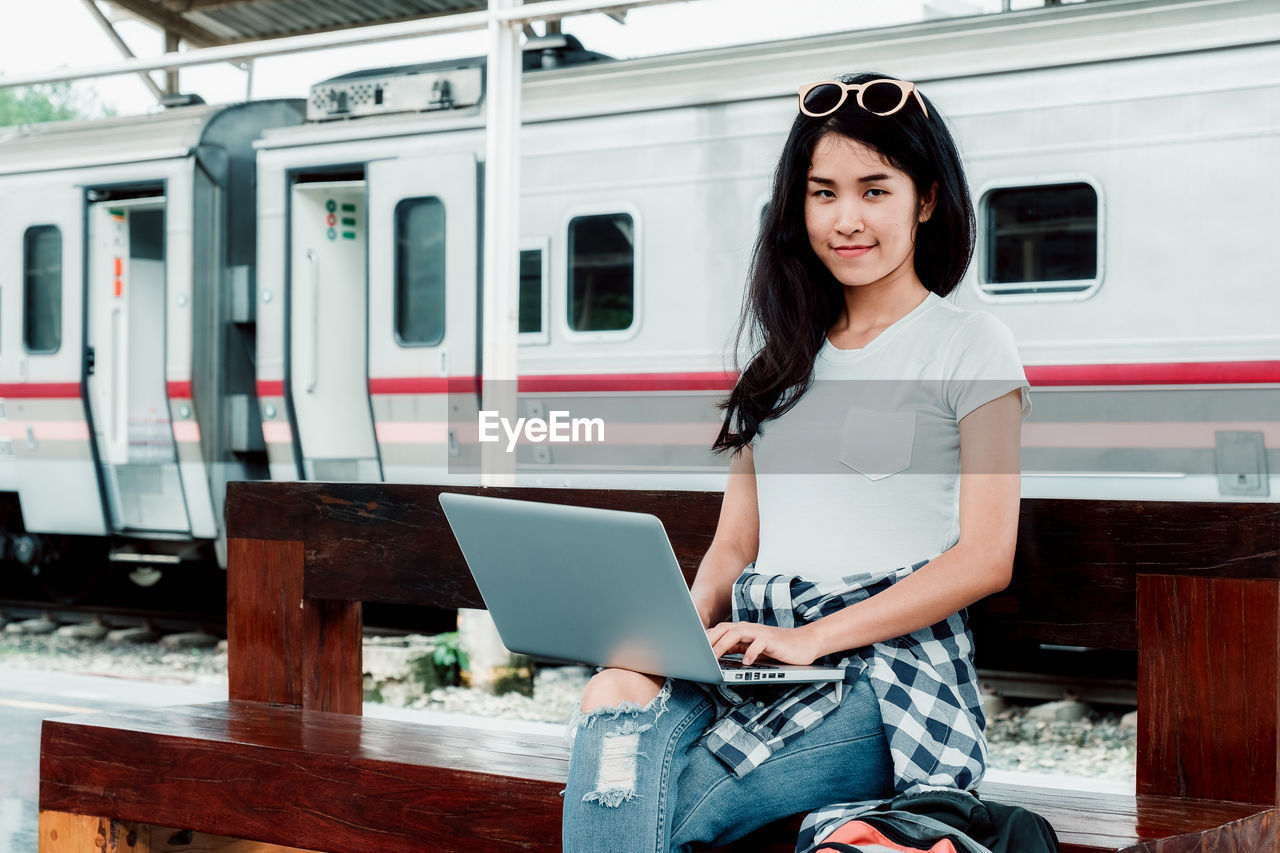 real people, one person, mode of transportation, transportation, public transportation, three quarter length, young adult, casual clothing, young women, technology, computer, looking at camera, women, hairstyle, rail transportation, lifestyles, communication, connection, train, wireless technology, using laptop, outdoors