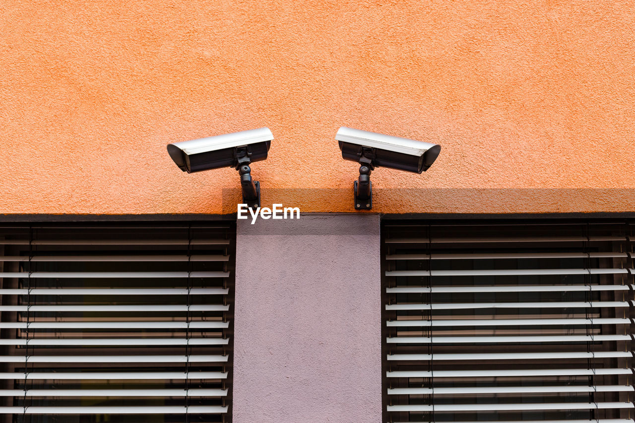 architecture, built structure, wall - building feature, building exterior, surveillance, security camera, no people, technology, day, outdoors, security, protection, safety, security system, low angle view, building, sunlight, wall, window, orange color, big brother - orwellian concept