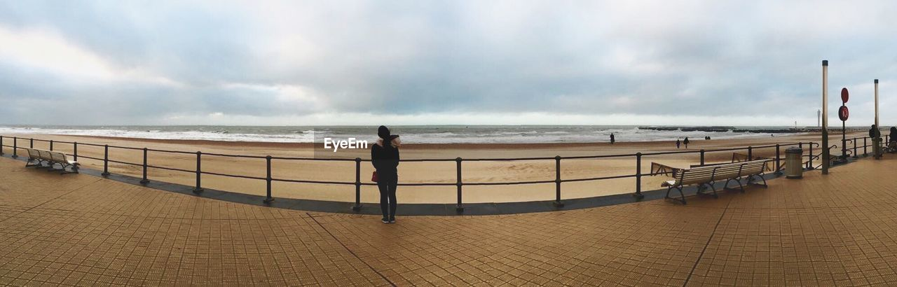 Panoramic Shot Of Woman Standing On Walkway Against Sea And Cloudy Sky