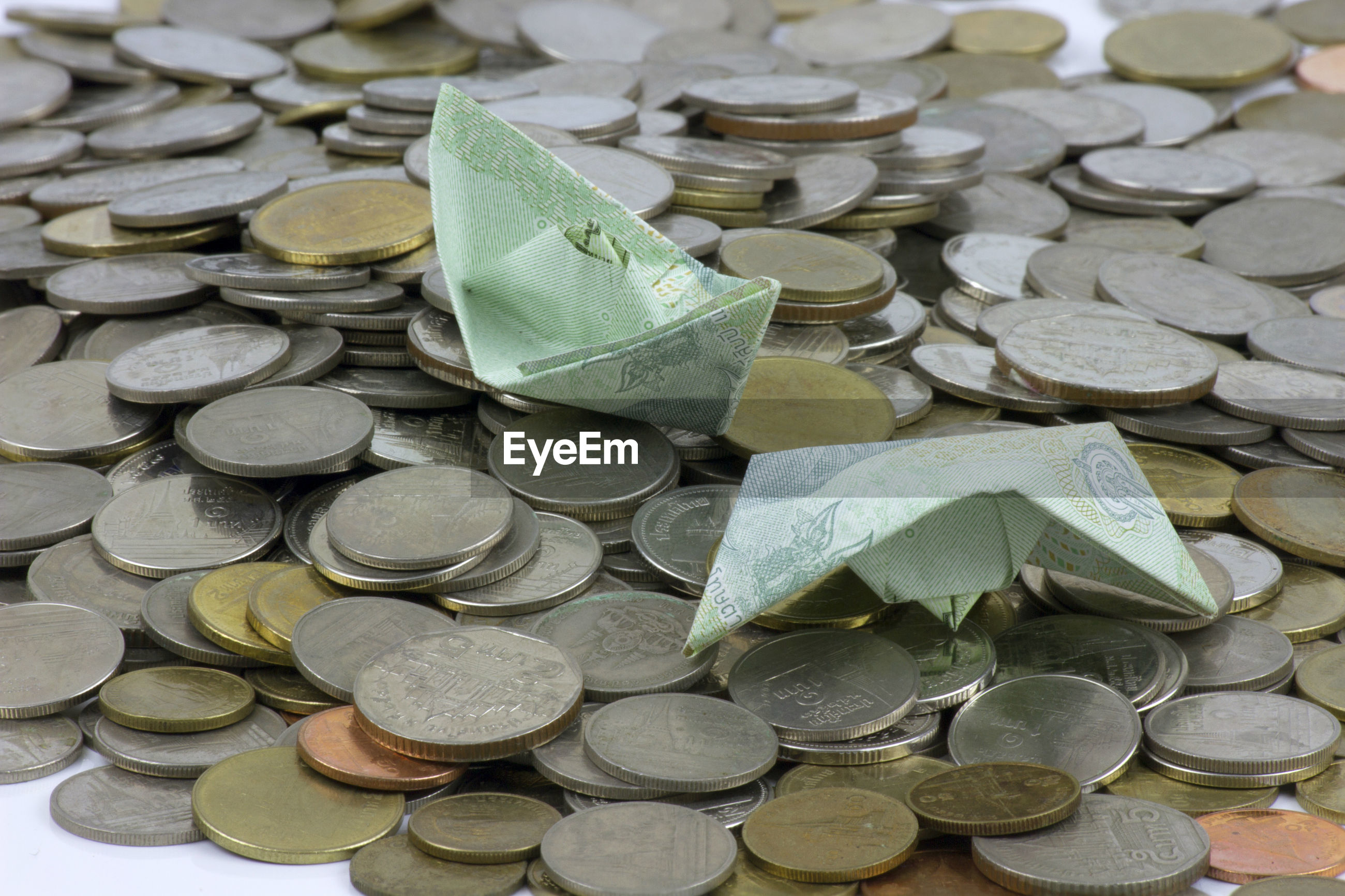 High angle view of paper boats on coins