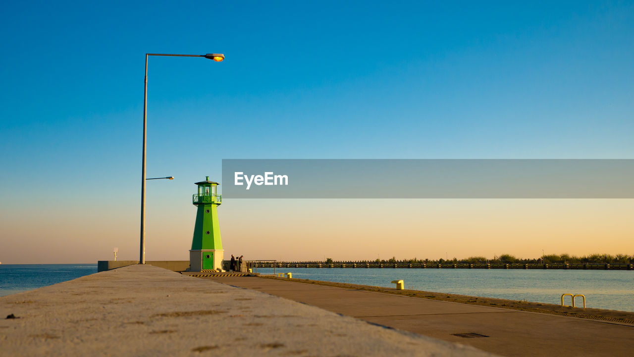 water, sky, sea, lighting equipment, direction, beauty in nature, nature, guidance, scenics - nature, safety, street light, beach, built structure, land, security, blue, architecture, clear sky, tower, lighthouse, no people, outdoors, horizon over water