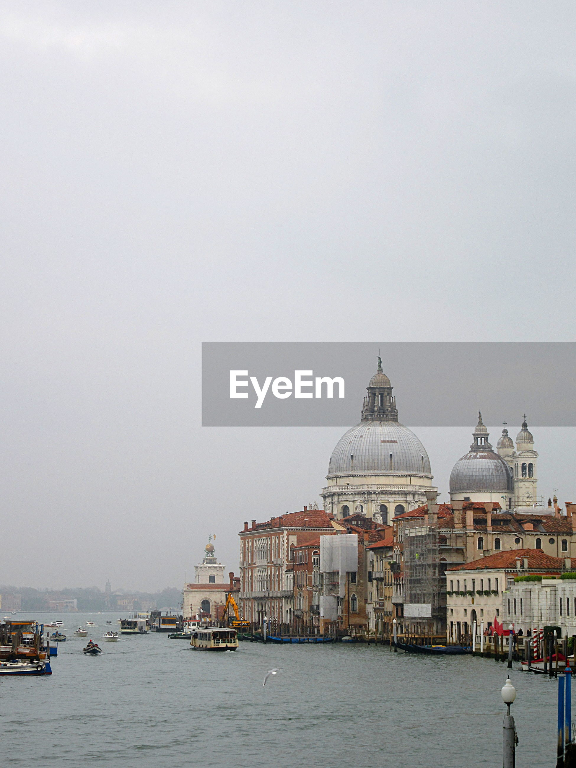 Santa maria della salute by grand canal against sky during foggy weather