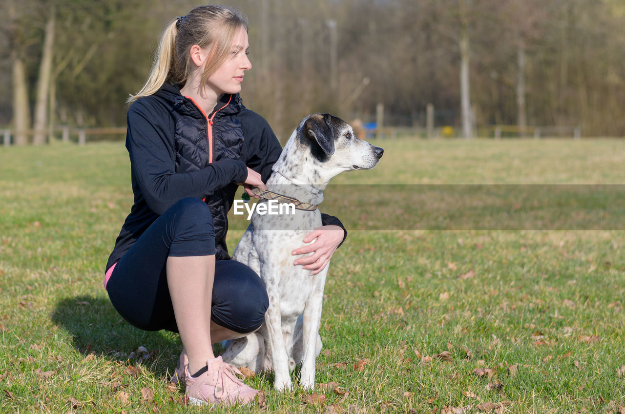 Woman with dog crouching on field