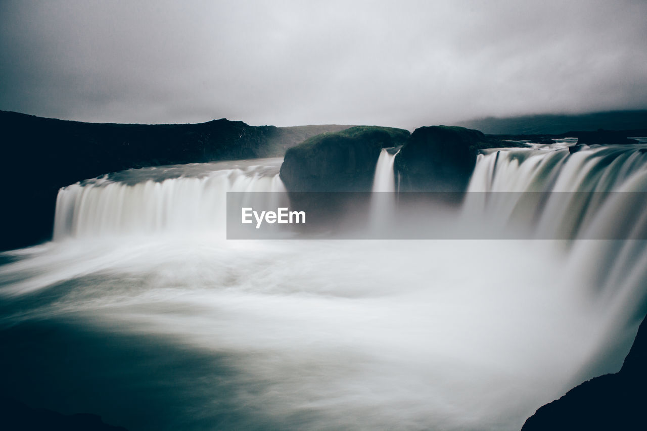 Scenic View Of Waterfalls Against Cloudy Sky