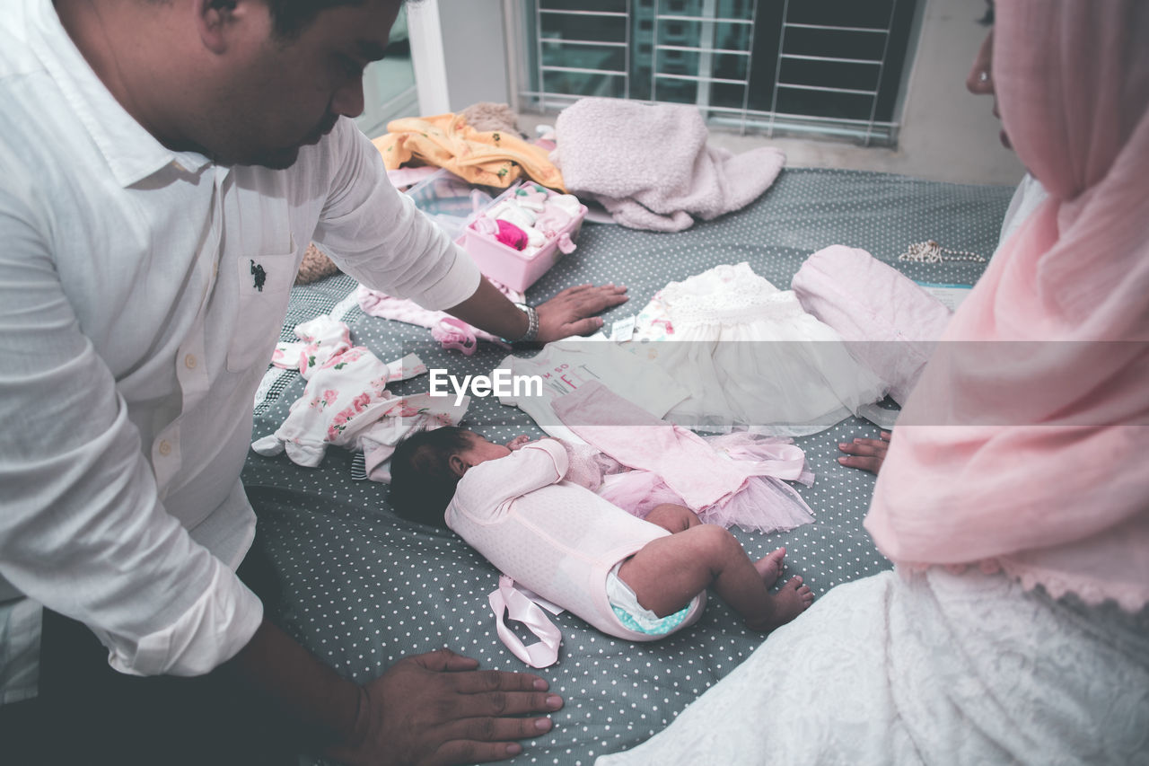 High Angle View Of Parents Looking At Baby Girl Sleeping On Bed At Home