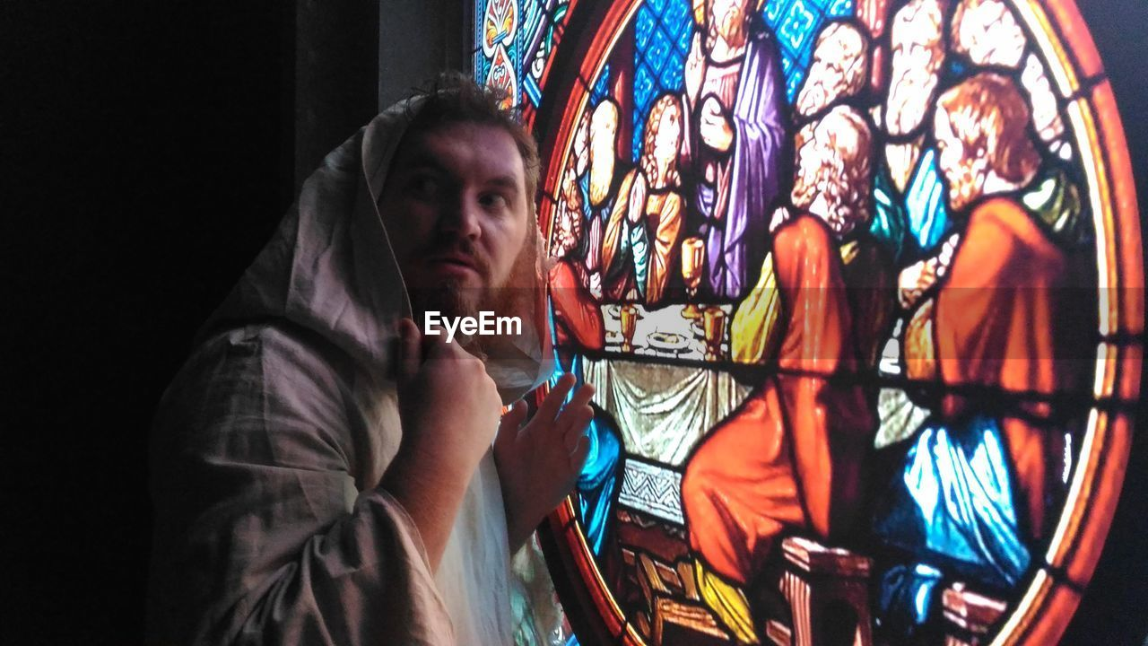 Priest Standing By Last Supper Stained Glass Window At Church