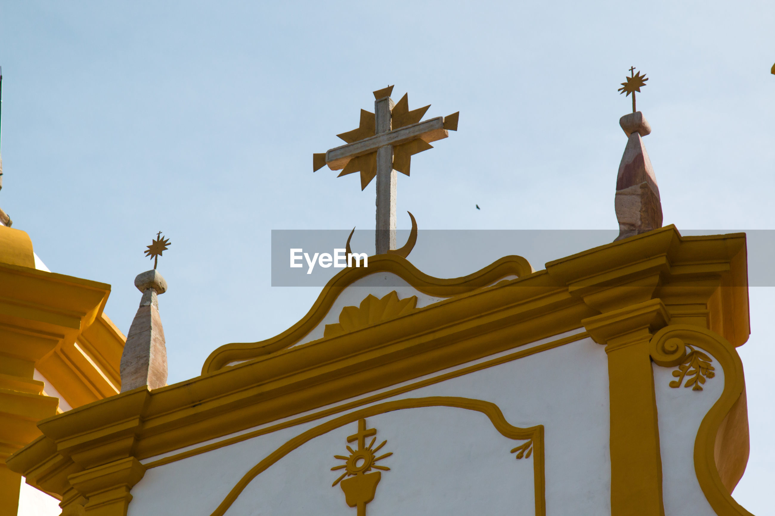 Low angle view of cross on igreja matriz church against sky