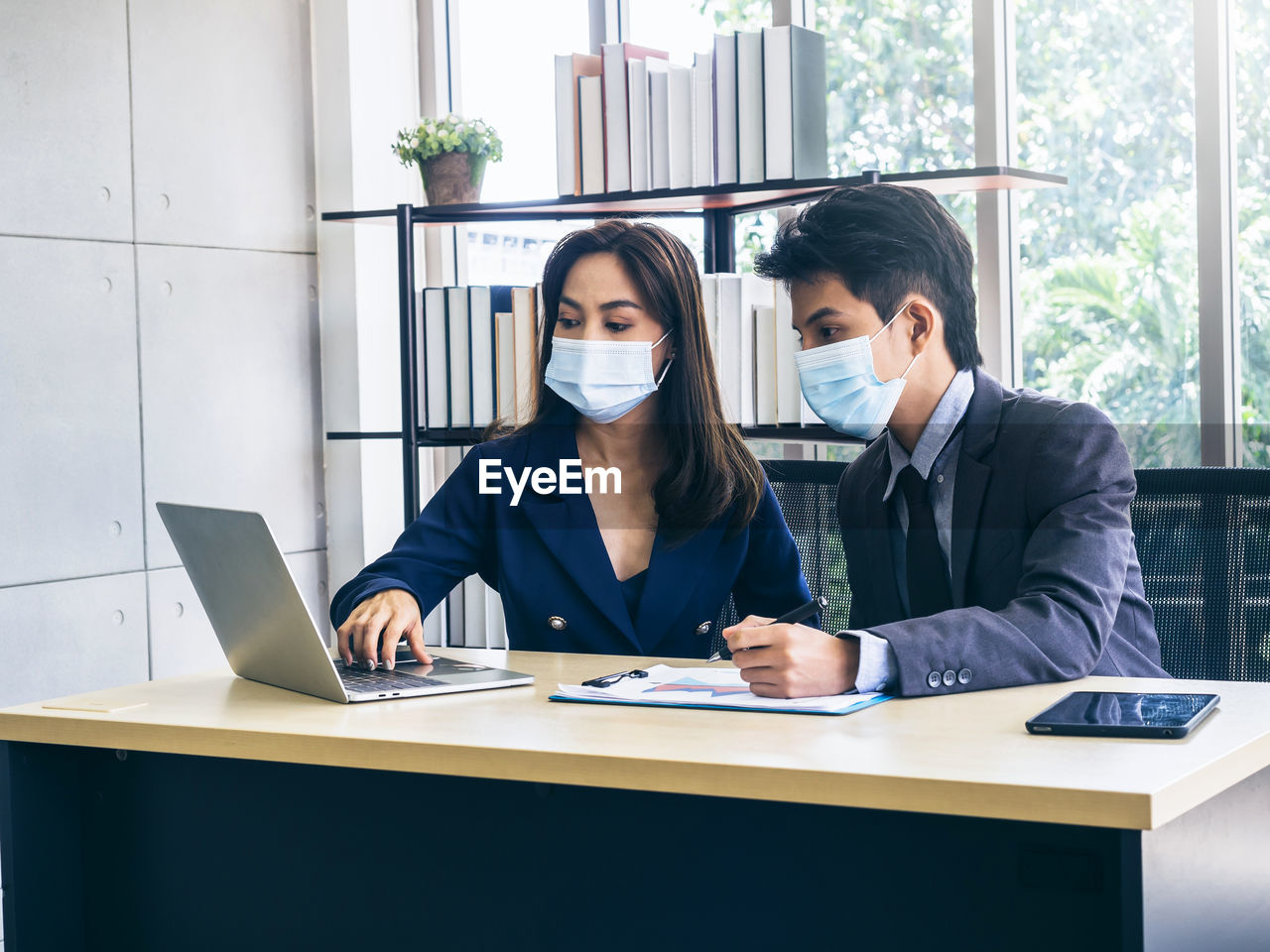View of business people wearing flu mask brainstorming at office