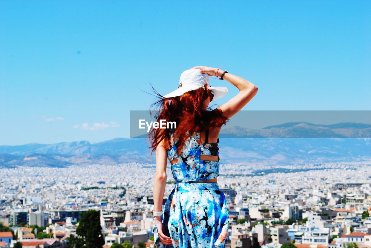 Rear View Of Woman Looking At City View Against Sky