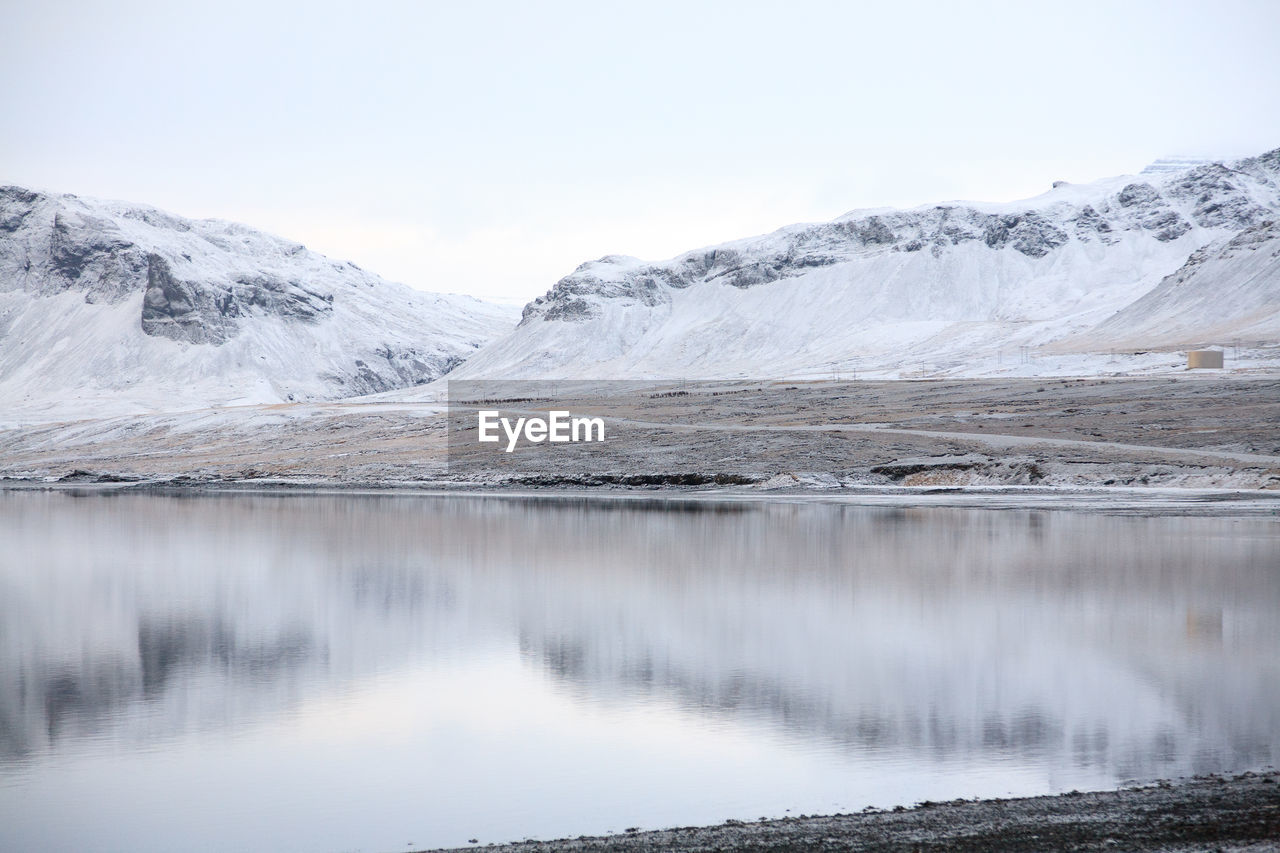 Scenic View Of Lake With Mountains In Winter