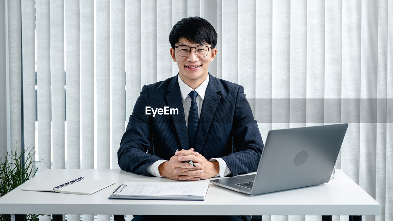 SMILING YOUNG MAN USING LAPTOP ON TABLE AT HOME