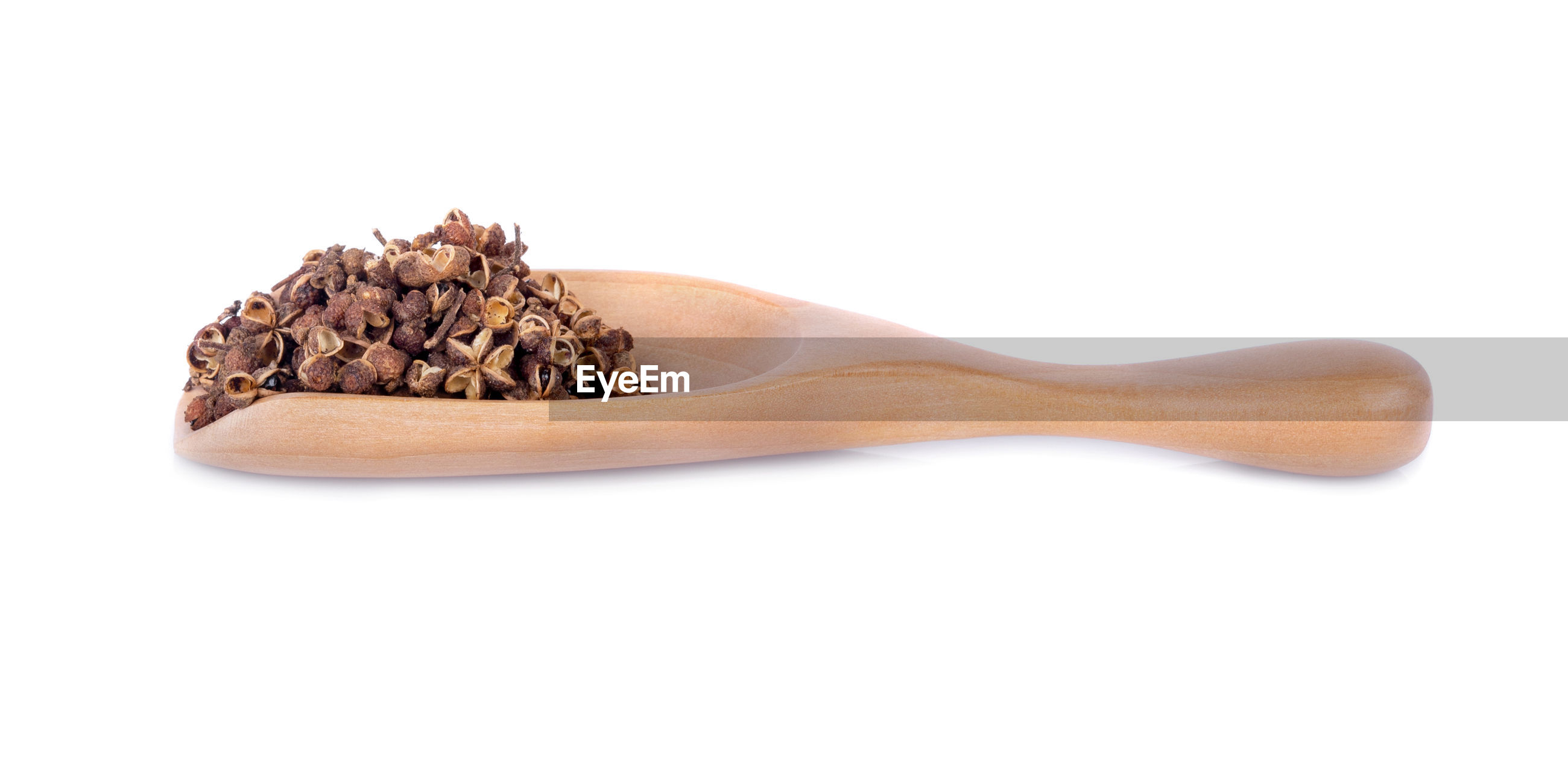 Close-up of spice in wooden spoon against white background